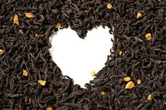 Heart shaped from black tea with passion fruit pieces on white background royalty free stock photos