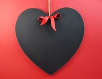 Heart shaped blackboard on a red background with copy space for your text here. Heart shaped blackboard with red ribbon on a red background with copy space for Stock Photography