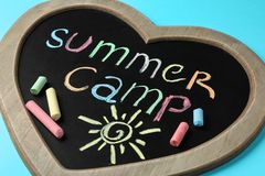 Heart shaped blackboard with text SUMMER CAMP, drawing and chalk sticks. On color background royalty free stock image