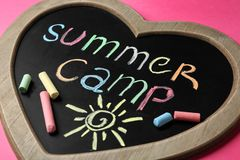 Heart shaped blackboard with text SUMMER CAMP, drawing and chalk sticks. On color background stock photo