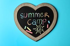 Heart shaped blackboard with text SUMMER CAMP, drawing and chalk sticks on color background. Top view stock photo