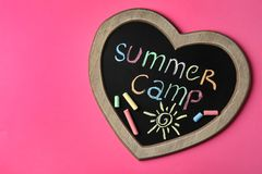 Heart shaped blackboard with text SUMMER CAMP, drawing and chalk sticks on color background, top view. Space for design stock photos