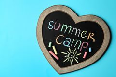 Heart shaped blackboard with text SUMMER CAMP, drawing and chalk sticks on color background. Space for design. Heart shaped blackboard with text SUMMER CAMP royalty free stock photography