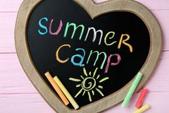 Heart shaped blackboard with text SUMMER CAMP, drawing and chalk sticks on wooden background. Flat lay stock photography