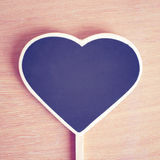 Heart shaped blackboard on wooden background Royalty Free Stock Photos