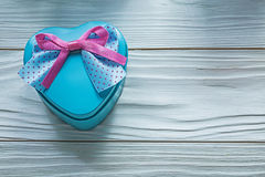 Heart-shaped blue gift box with pink bow on wooden board holiday Stock Images