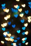 Bokeh background with unique heart shaped  lights or blurred lights background. Heart shaped blurred lights in various shades of blue,green, teal, red, yellow Stock Photos