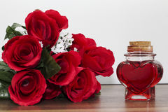 Heart shaped bottle next to a bouquet of roses Royalty Free Stock Images