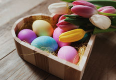 Heart shaped bowl, colored eggs and tulips - happy Easter Royalty Free Stock Photos