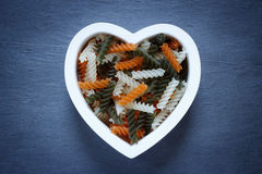 Heart shaped bowl filled with Tri Color Fusilli Stock Image