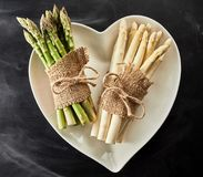 Heart shaped bowl with fresh asparagus spears stock photography