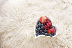 Heart shaped bowl full of berries and standing in sheep skin from top view Royalty Free Stock Image