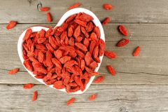 Heart shaped bowl of goji berries on wood Stock Image