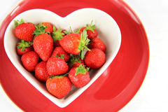 Heart shaped bowl of juicy red strawberries. On red plate on white background Stock Photo