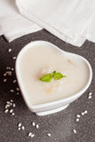 Heart-shaped bowl of rice pudding with fresh mint Stock Photos