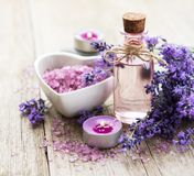 Heart-shaped bowl with sea salt, oil  and fresh lavender flowers. Heart-shaped bowl with sea salt, oil and fresh lavender flowers on a old wooden background stock photography