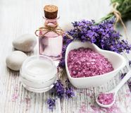 Heart-shaped bowl with sea salt, oil  and fresh lavender flowers. Heart-shaped bowl with sea salt, oil and fresh lavender flowers on a old wooden background stock photos