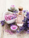 Heart-shaped bowl with sea salt, oil  and fresh lavender flowers. Heart-shaped bowl with sea salt, oil and fresh lavender flowers on a old wooden background royalty free stock image