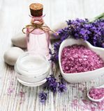 Heart-shaped bowl with sea salt, oil  and fresh lavender flowers. Heart-shaped bowl with sea salt, oil and fresh lavender flowers on a old wooden background stock images