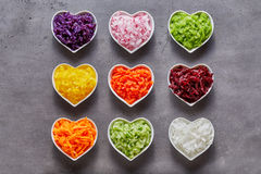 Heart-shaped bowls with healthy ingredients. Heart-shaped bowls with healthy grated vegetable ingredients of different colors shot from above on grey background Royalty Free Stock Photos