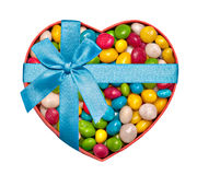 Heart-shaped box. Filled with colorful candies and tied with blue ribbon and bow stock photography