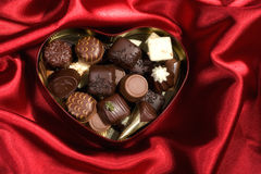 Heart Shaped Box of Candy on red satin background Royalty Free Stock Photos