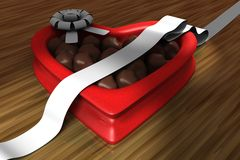 Heart Shaped Box of Chocolates. Red heart shaped box of chocolates on hard wood surface with a white ribbon Royalty Free Stock Photos