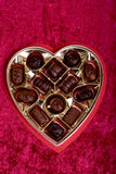 Heart Shaped Box of Chocolates. A heart shaped box of chocolates over a red background royalty free stock images