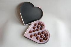Heart-shaped box of chocolates. A heart-shaped box, with round chocolates in it Royalty Free Stock Photos