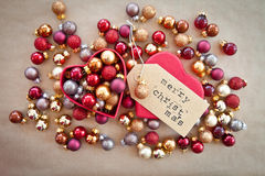 Heart shaped box with christmas baubles. Red heart shaped bow with shiny christmas baubles Stock Photo