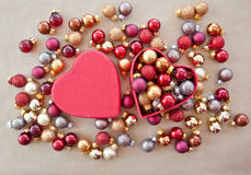 Heart shaped box with christmas baubles. Red heart shaped bow with shiny christmas baubles Royalty Free Stock Photography