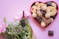 Heart shaped box with cookies and flowers. Gifting theme image with a red heart shaped box full of delicious sweets and a bouquet of flowers on a pink background Royalty Free Stock Photos