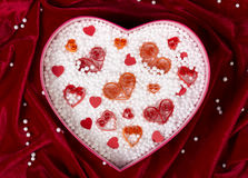 Heart-shaped box filled with small foam balls and handmade paper hearts. On red velvet tablecloth. Top view. Romantic background. Packing for fragile items Royalty Free Stock Photography