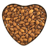 Heart shaped box full of almonds. Heart shaped box full of almond nuts isolated over white background, top view Stock Photos