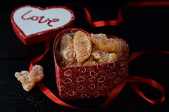 Heart shaped box full of candied orange slices. Lid in a shape of heart with love word, red ribbon on a black background Royalty Free Stock Photos