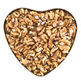 Heart shaped box full of walnuts. Heart shaped box full of walnut nuts isolated over white background, top view Royalty Free Stock Photo
