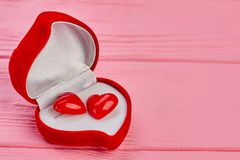 Heart shaped box with gift. Red opened velvet box with female earrings and copy space. Happy Valentines Day Stock Photo
