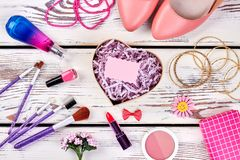 Heart-shaped box. With blank card on a dressing table. Diversity of cosmetic products, tools and jewelry Stock Image
