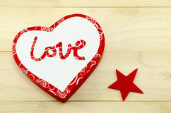 Heart shaped box and a red star. On a wooden table Royalty Free Stock Photo
