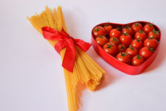Heart shaped box of red tomatoes and spaghetti tied with a red r stock photography