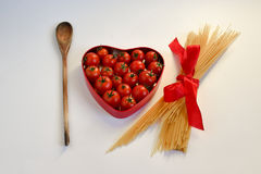 Heart shaped box of tomato, wooden spoon and spaghetti tied with an ribbon Stock Image