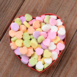 Heart Shaped Box with Valentines Candies. High angle view of a heart shaped box filled with Valentine's Day Candies. The box in the middle of a rustic wood stock image