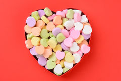 Heart Shaped Box with Valentines Candy. High angle view of a heart shaped box filled with Valentine's Day Candies. The box in the middle of a red background. The stock photos