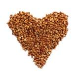 Heart shaped brown buckwheat, valentine heart of brown groats. I Stock Photos
