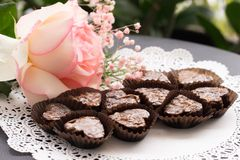 Heart shaped Brownies. In glassine brown cups served on a lace doily and decorated with a white rose with pink borders and gypsophilas royalty free stock photo