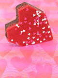 Heart Shaped Brownies with Heart Sprinkles (8.2mp Image). Heart shaped brownie with red icing and white and pink sprinkles on a pink placemat. Shot with a Canon royalty free stock image