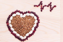 Heart-shaped buckwheat with beans on wooden background Royalty Free Stock Image