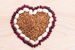Heart-shaped buckwheat with beans on wooden background Stock Photo
