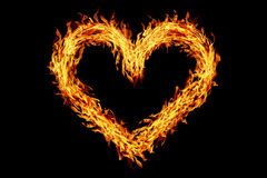 Heart shaped burning fire isolated on black Stock Images
