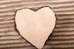 Heart shaped burnt out of a cardboard Stock Photography